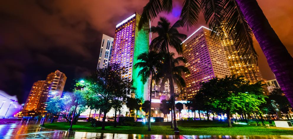 Palms and colorful skyscrapers in downtown Miami at night. Southern Florida, USA. Photo: Getty Images