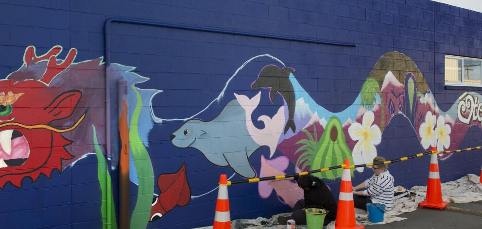 Dunedin artist Claire Rye paints a mural on a wall at Cargill Enterprises, in South Dunedin,...