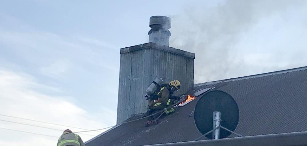 Firefighters work to put out a chimney fire in the Wrinkly Rams, Omarama. PHOTO: SUPPLIED
