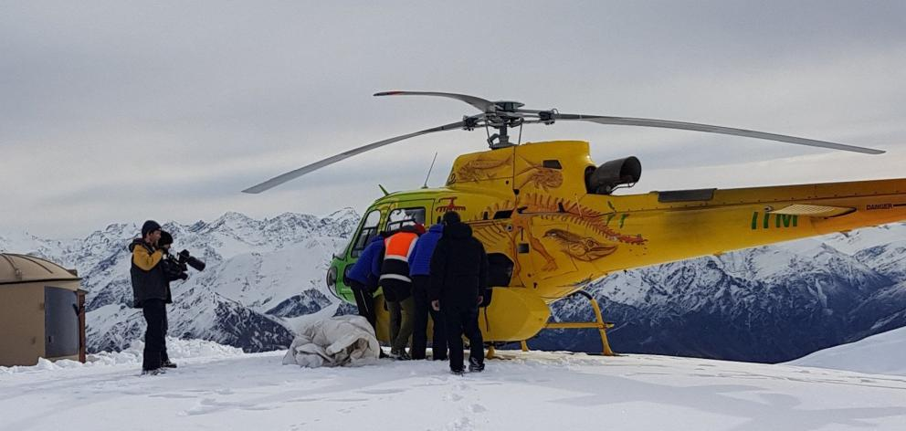 Unloading the helicopter at Mt Saint Just while film-maker Mark Johansson looks on. PHOTOS: ERIK...