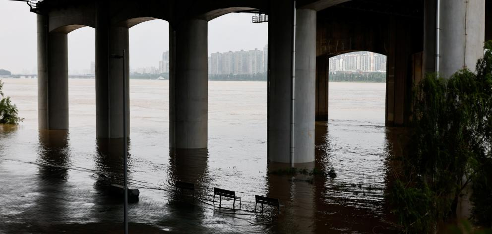 Partially submerged benches at a Han River Park in Seoul. Photo: Reuters