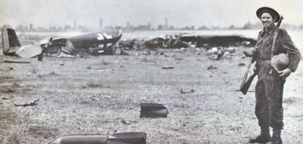Sapper Phillip Bradley stands by the wreckage of a German aircraft  in Greece during World War 2....