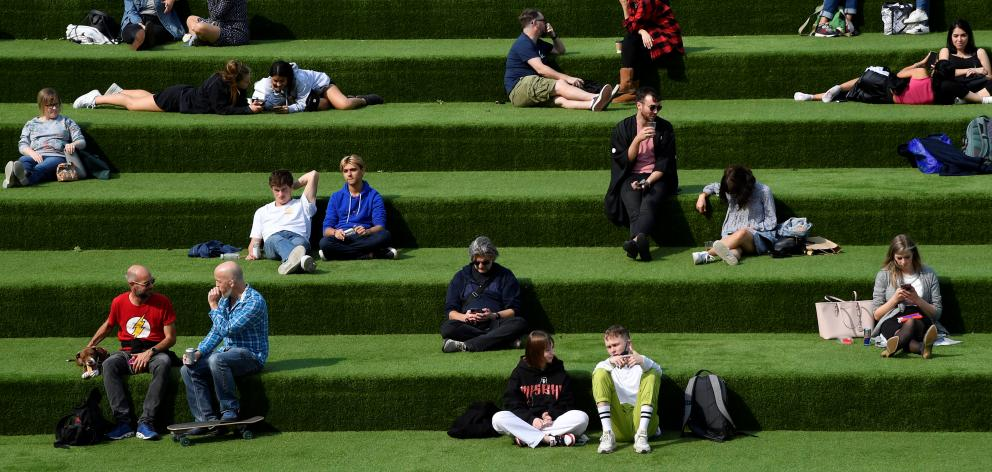 People are seen relaxing in an outdoor seating area while social distancing in London. Photo: Reuters