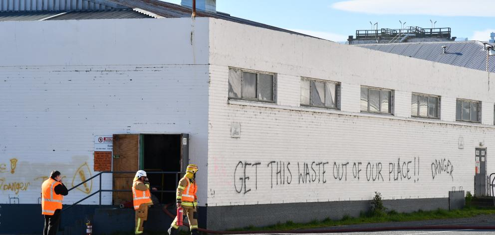Firefighters at an entrance to the building holding toxic ouvea premix in Mataura. PHOTO: LAURA...