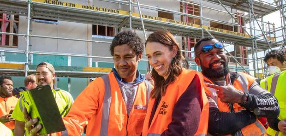Prime Minister Jacinda Ardern poses for selfies with tradesmen at Isles Construction in Palmerston North last week. Judith Collins claims Ardern is breaking her own rules. Photo: NZ Herald