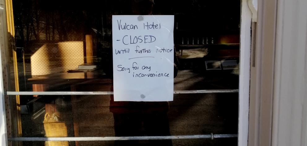 A sign on a window says the historic Vulcan Hotel is closed.