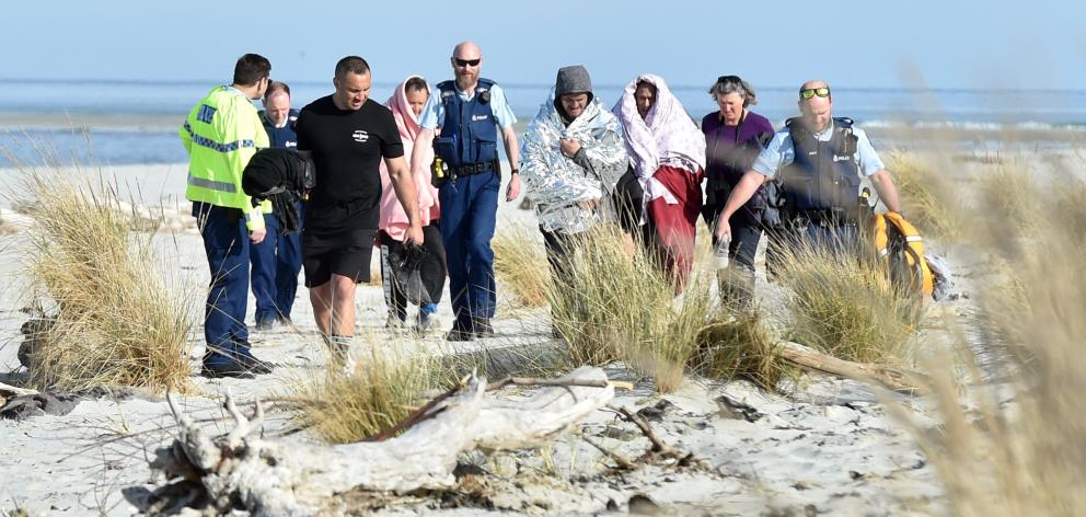 Three boat accident survivors swathed in blankets are accompanied by police officers and members...