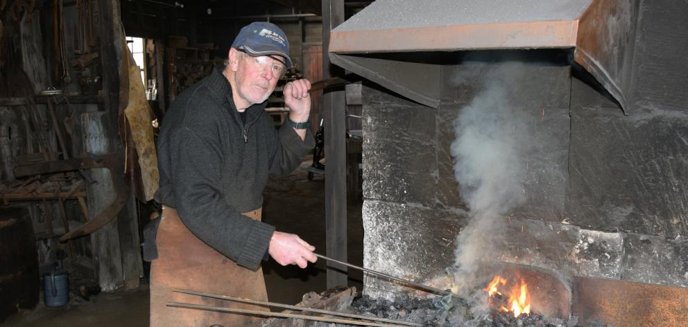Nicol's Blacksmith Shop volunteer John Stannard heats metal in a forge in Duntroon.