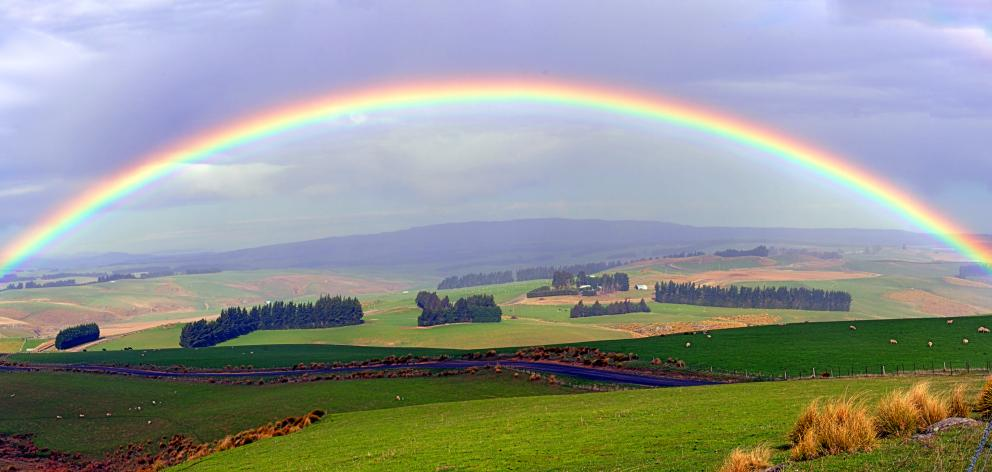 A rainbow appears between the Lammerlaw and Maungatua ranges.