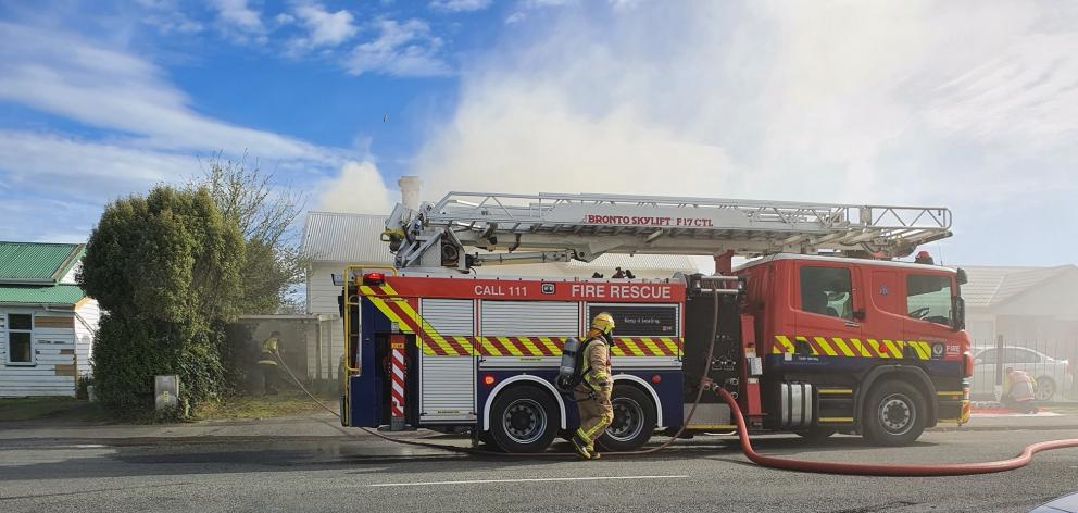 Smoke rises from a house in Ettrick St as firefighters respond to a blaze at the back of the dwelling. Photo: Gail Campbell