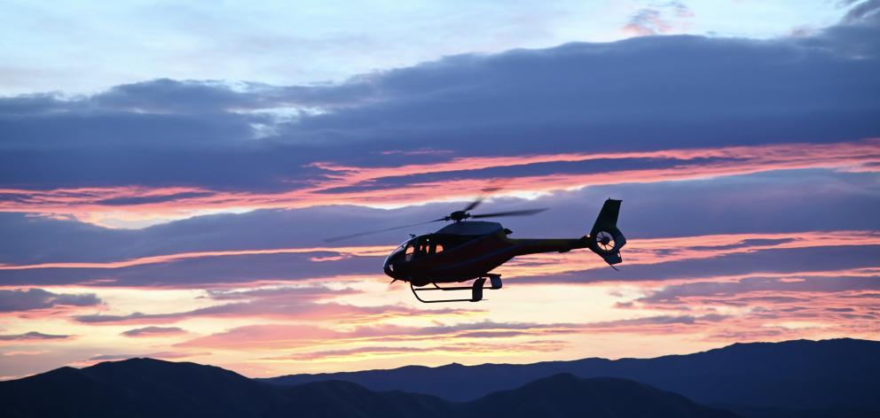 A helicopter takes off at first light to tackle the Lake Ohau fire. Photo: Craig Baxter