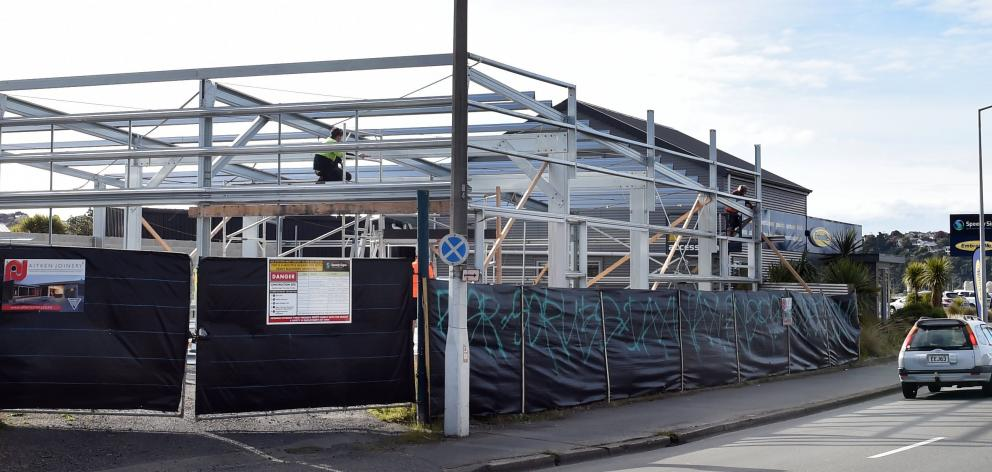 Builders work on the first of three new commercial buildings going up in Portsmouth Dr. The...