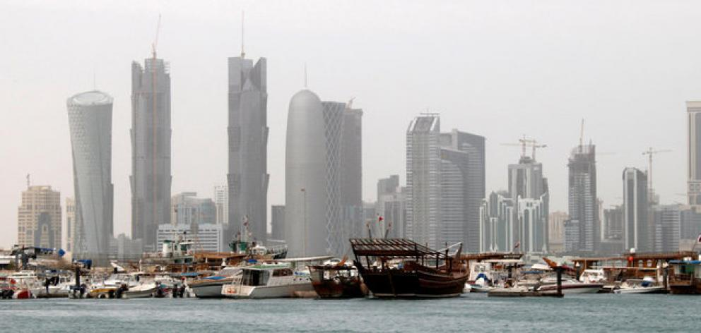 Traditional fishing Dhows are seen in port near modern glass and steel buildings on the Doha skyline. Photo: Reuters