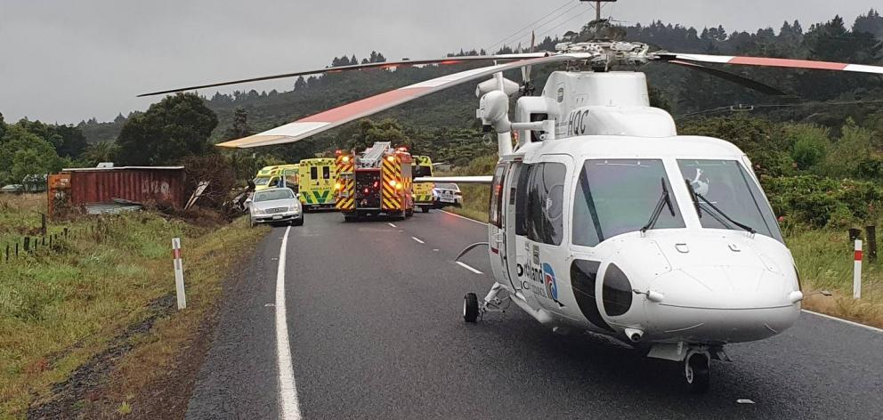 The Northland Rescue Helicopter at the crash scene on SH12 near Omanaia. The shipping container struck by the car can be seen on the left. Photo: NEST