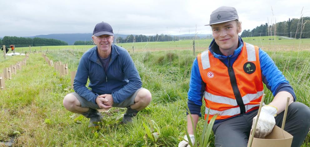 Project manager Shane Bocock (left) checks in with Habitat Restorations worker Gabriel Kennedy Atchisonas he plants flax on the bank of the Washpool Stream. PHOTO: RICHARD DAVISON