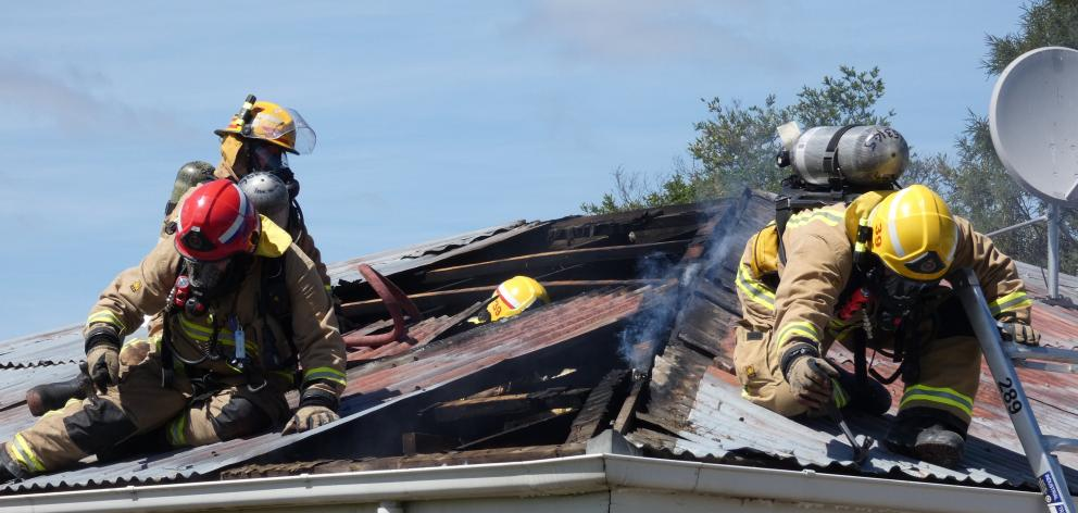 Firefighters lift roofing iron to tackle hot spots at a house fire at the corner of Ventry and...