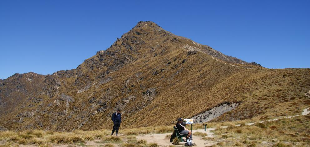 Trampers have a rest on Ben Lomond Saddle with the peak towering above them. PHOTO: ALINA SUCHANSKI