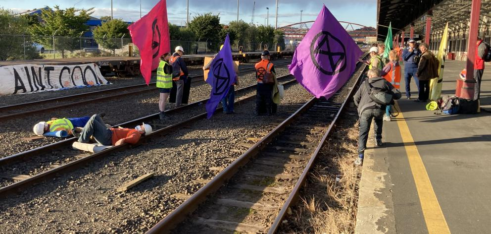Activists against coal mining lay on the tracks at the Dunedin Railway Station this morning. Photo: Stephen Jaquiery