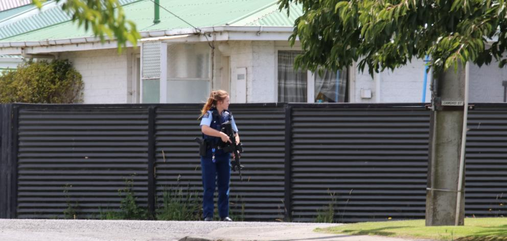 An armed police officer on corner of Oxford St and Hamilton St earlier this afternoon. Photo:...