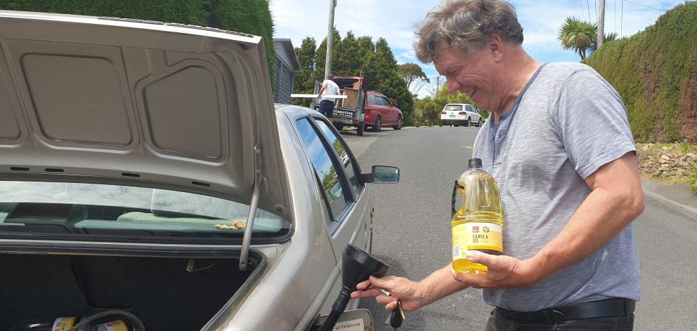 Simon Blake refuels his vegetable oil-powered car for the trip to Dunedin  from Broad Bay.