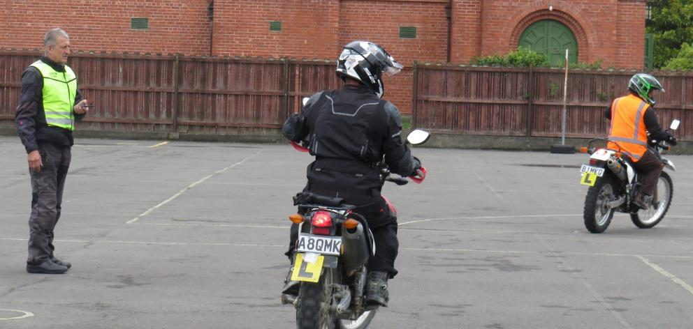 Motorcycle training instructor Clive Chapman watches and communicates with bronze course...