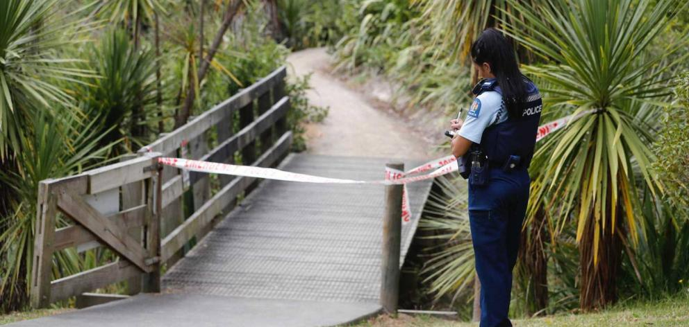 An officer guards a walkway  where a man was found in the water at Meola Creek, Westmere, this...