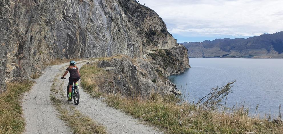 Lisa Scott cycles along the Dingleburn bluffs above Lake Hawea. Photo: James Mitchell