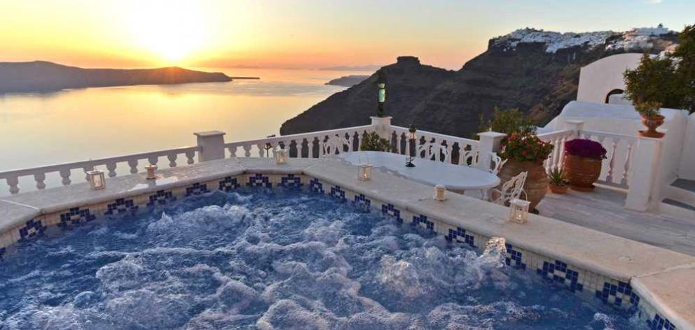Sunset from the jacuzzi at our Santorini Love Home Swap with Skaros Rock and the villages of...