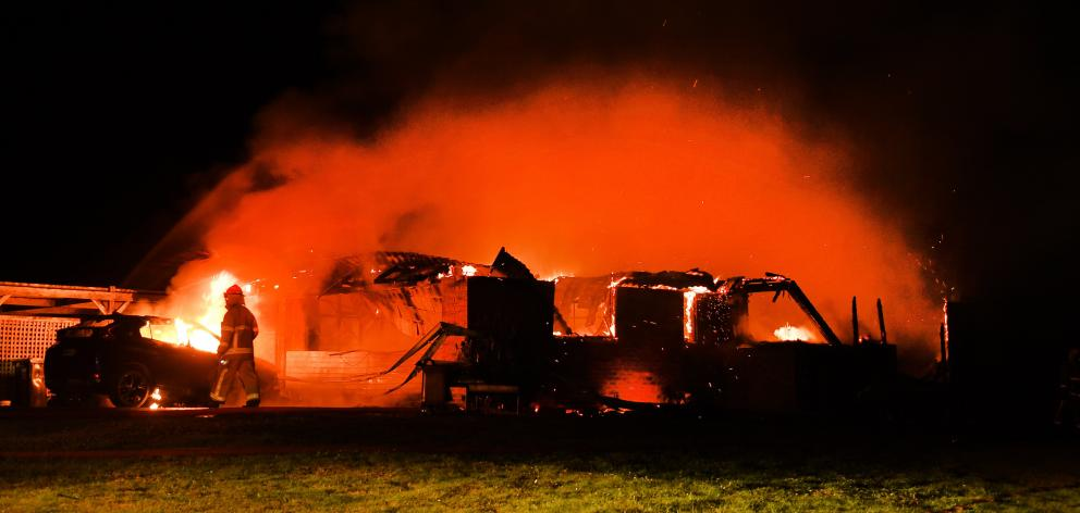 Flames engulf the Waitati house as firefighters do what they can. PHOTOS: STEPHEN JAQUIERY