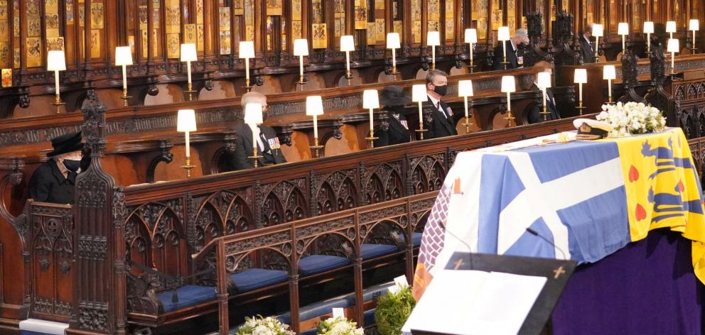 The Queen watches as the coffin of Prince Philip is placed inside St George's Chapel at Windsor...
