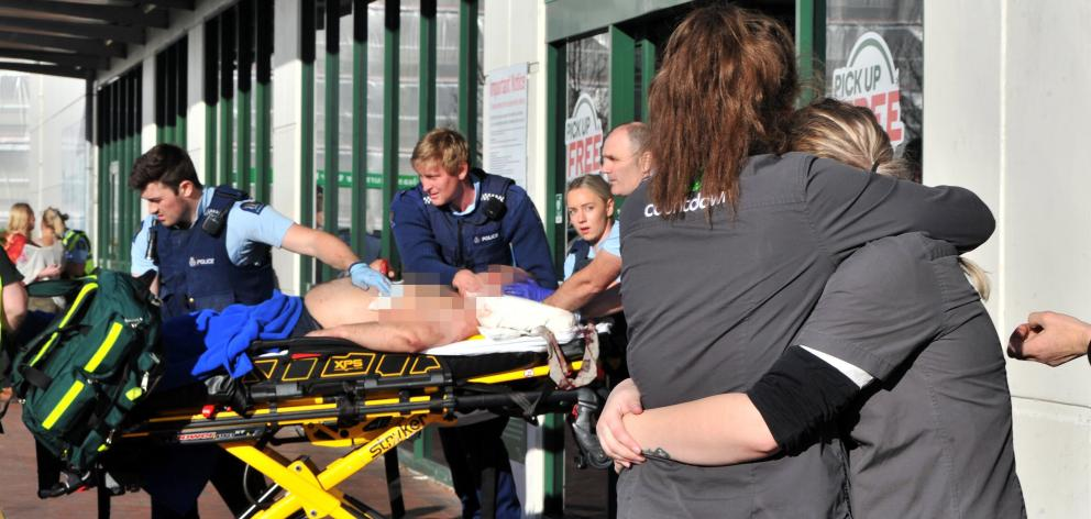 Countdown staff comfort each other as a stabbing victim is rushed to an ambulance outside the...