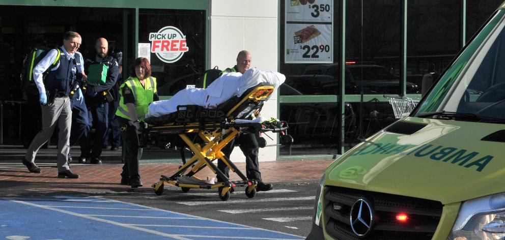 A patient is wheeled to an ambulance after the stabbing in Countdown Dunedin Central today. Photo: Christine O'Connor