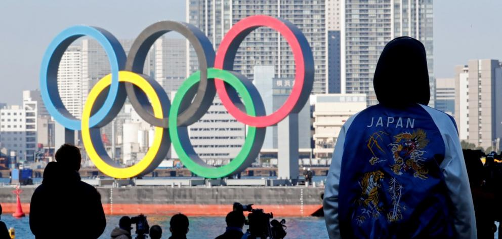 Bystanders watch as giant Olympic rings are reinstalled at Tokyo's Odaiba Marine Park in December...