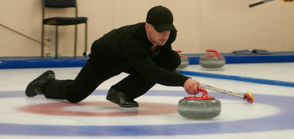Anton Hood delivers a  stone during a match at the New Zealand Curling Championships in Naseby ...