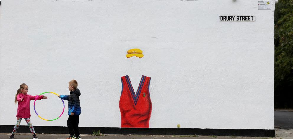 Children play next to a mural in Darlington, England, dedicated to British US Open winner Emma...