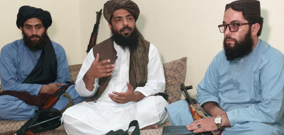 Waheedullah Hashimi (centre) says the Taliban would  fully implement its version of sharia, or...