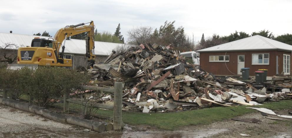 An excavator finishes demolishing The Bank Ophir after it was gutted by fire yesterday. PHOTO:...