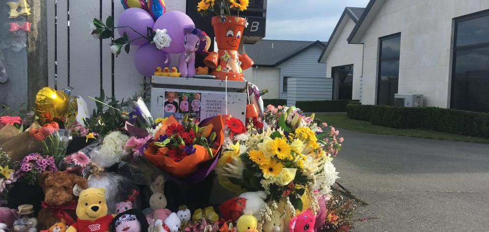 An ever-increasing collection of flowers and toys have been laid on the driveway of the Queen St home where three children were killed last week. PHOTO: HELEN HOLT
