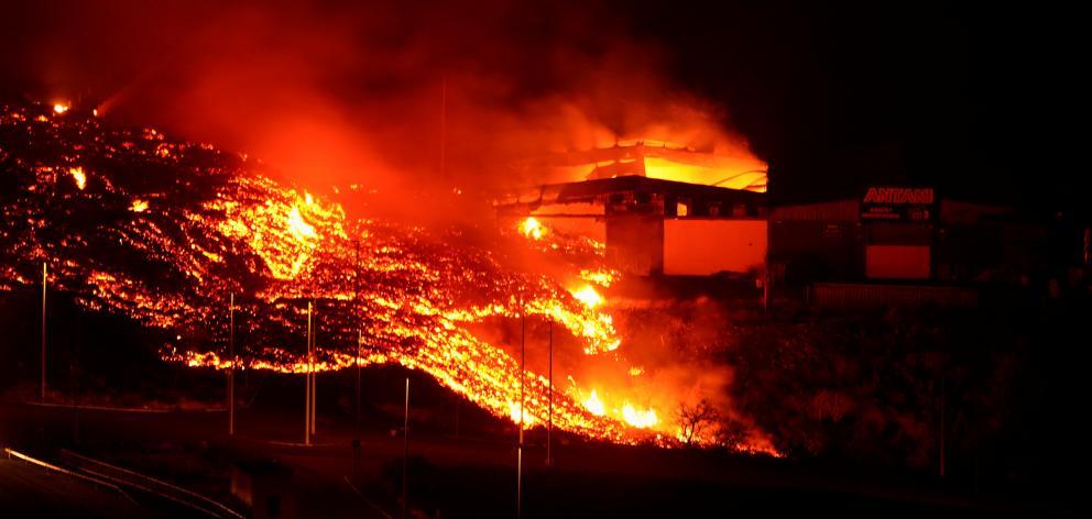 Lava burns buildings following the eruption of the Cumbre Vieja volcano. Photo: Reuters