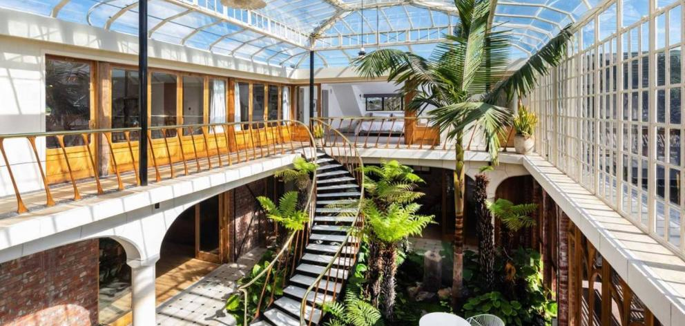 The spectacular glass conservatory and curved marble staircase. Photo: Supplied