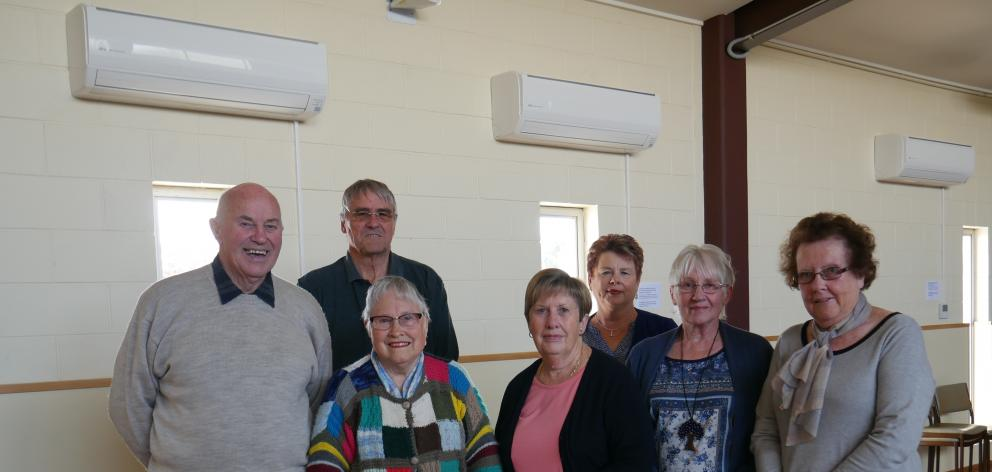 Standing in front of the new heaters they recently bought for the Senior Citizens Hall are (back...