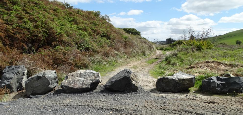 A row of large rocks, which the Department of Conservation has placed across the entrance to an...