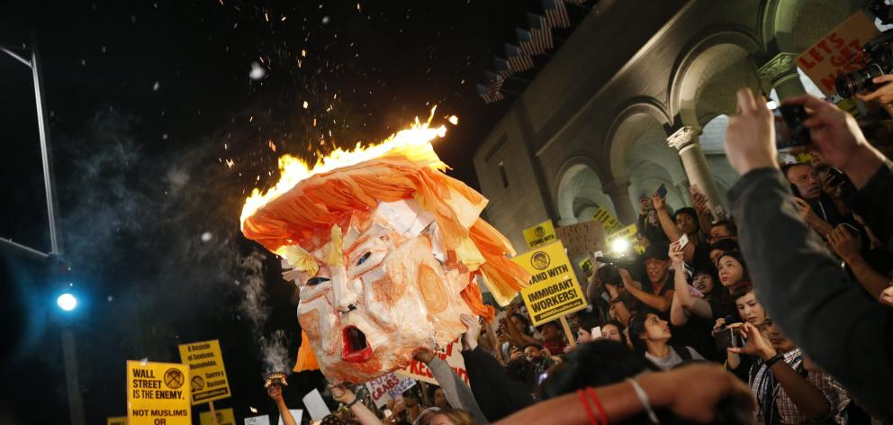 Protesters burn an effigy of Donald Trump outside Los Angeles City Hall. Photo: Reuters
