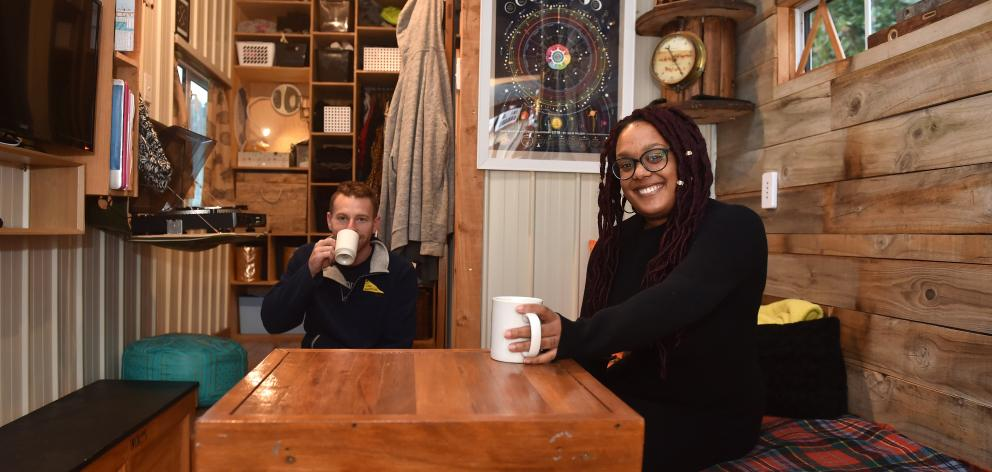 Patrick Brunelle (32) and Cori Holmes (28) relax in their tiny home, which is off the grid and...