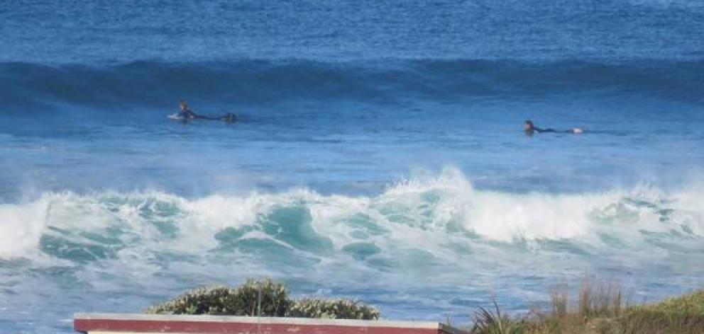 A couple of surfers had decided to head out on their boards this morning. Photo: Ken Cashin via...