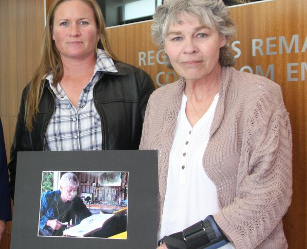 Midge Henderson (right) and her daughter Sarsha Allen hold a photograph of Ms Henderson's partner...