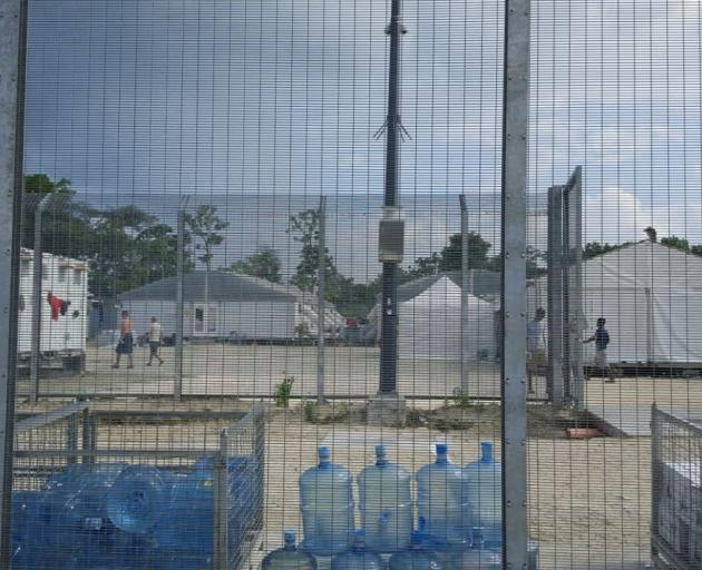 Detainees walk around the compound near a stack of water bottles inside the Manus Island...