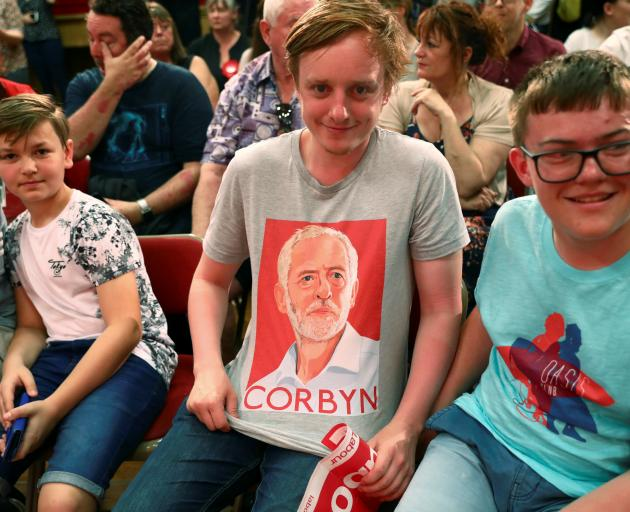 A supporter waits for Jeremy Corbyn, leader of Britain's opposition Labour Party, to give a...
