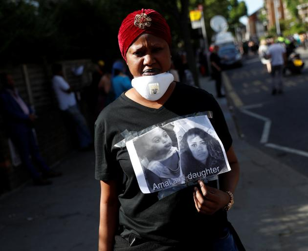 A woman with a poster of missing people. Photo: Reuters