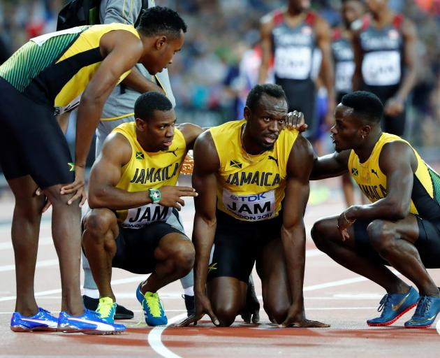 Bolt was later helped off the track by his team-mates cheered on by a huge crowd. Photo: Reuters